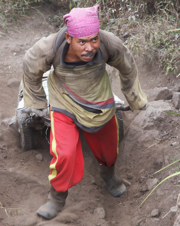 A miner struggles to haul his cart up a rise in the ground.  Most of the journey is downhill, but there are some bumps.