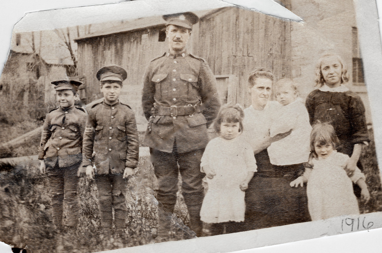 "The White Family in 1916: Though already in his early 40s and despite initial rejections, Tommy's father had finally convinced the Army to let him enlist. In the backyard of their Kingston Ontario home, seven-year-old Tom Jr. poses ""in uniform"", flanked by his equally patriotic younger brother Jimmy and their father, as the senior Thomas White prepares to leave his growing family and re-cross the Atlantic -- barely eight years after he & Lizzie (with their daughter Mary, at right) had first arrived from Scotland. <br /> <br /> Tommy's father served as a medical support worker in England for about a year and a half, after a previously-sustained foot injury rendered him unfit for active duty. When on leave, he traveled north to visit friends in Greenock, and sent picture postcards to ""Mrs. White"" back in Canada, with nostalgic views of their old home town."