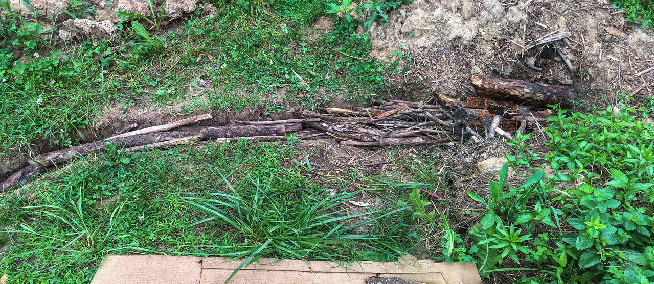 This log pile is in a narrow ditch that mostly drains kitchen garden bed 2.  It will be covered with the clayey soil and tamped down to prevent a lot of air getting downto the logs so that decay will slow and let this continue to serve as drainage help.  Don't plan to plant things here, this crosses an access path.  The right or north end is inside garden bed 1 and that will be treated like a normal logpile berm, with layers of mulch and sticks and stuff built up above the ground level.