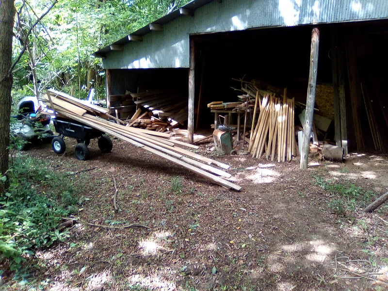 Moving the floor boards from Mansfield around to the storage shed.  Note wheels of trailer off ground.  second load tipped the trailer and bent the tonue a bit.  and dropped the board, fortuantely close to where I was going anyway.