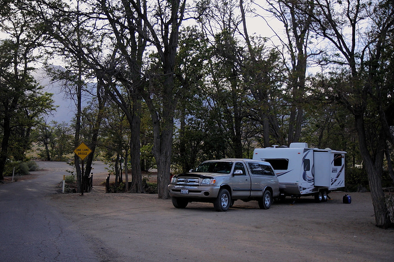 """Here's Tinnemaha Campground, on the east side of Hwy 395 opposite Tinnemaha Reservoir. That's Tinnemaha Creek running through the campground. It's a bare-bones site, but I wanted to try my trailer's """"boondocking"""" capabilities, i.e., to be self-contained and not have to worry about facilities or power. You can see my new generator sitting on the ground to the right of Discovery. It's a Yamaha EF2000iS, meaning it can generate up to 2000 watts of power. It proved to be plenty powerful -- and very quiet for a generator with its output --  though I did have to shut off an appliance or two as I could tell it was straining. And I've read that the power output decreases by 3% with every 1000 feet of altitude gain -- and the campground is at approximately 4000 feet."""