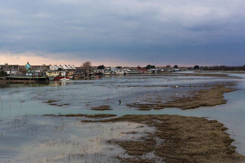 The collection of house boats stretched out along the banks of the river Adur at high tide. Shoreham-By-Sea, Sussex, UK. April 2016.
