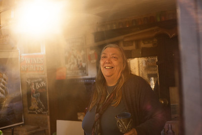 Polly Cole behind her bar in the hull of her home. Shoreham-By-Sea, Sussex, UK. April 2016.