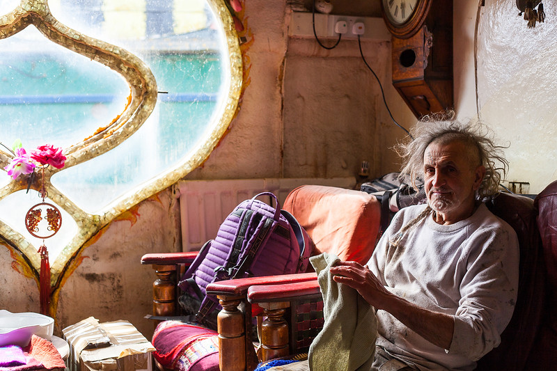 Hamish sitting to clean his hands after a day working on boat repairs. Shoreham-By-Sea, Sussex, UK. April 2016.