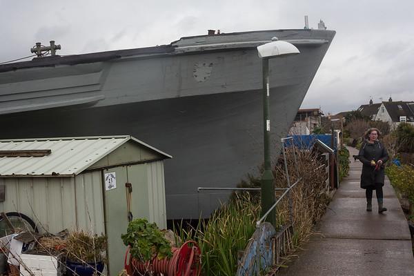 The bow of 'Fische' protruding onto the slim tow path that connects the house boat community. Shoreham-By-Sea, Sussex, UK. April 2016.