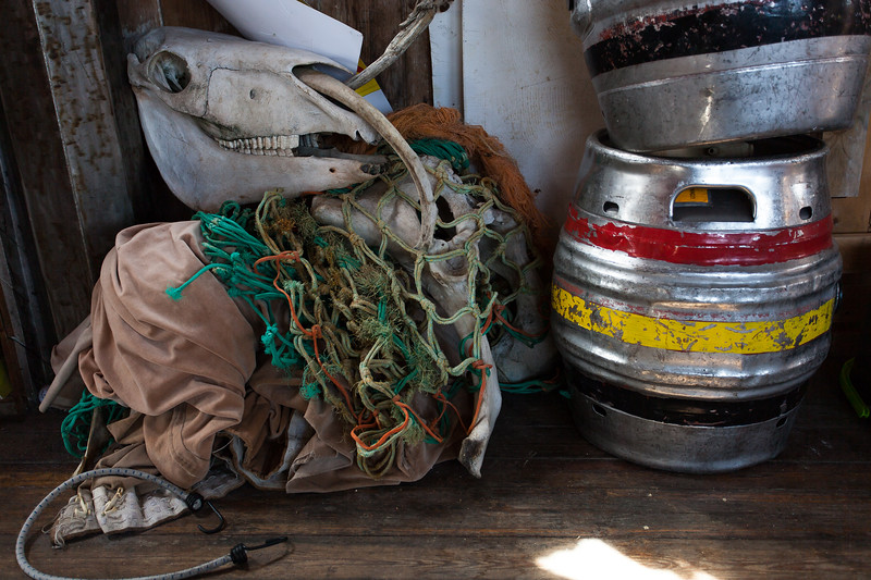 A Skull, fishing nets and beer barrel on the deck of Hamish's Home. Shoreham-By-Sea, Sussex, UK. April 2016.