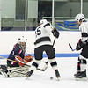 Longmeadow forward Jordan Kowalski tries to deflect the puck past the Medway goalie