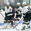 Longmeadow defensive players Jillian Beaulieu (18), Katherine Guidrey (3) and forward Ashley Barron (9) surround the Medway puck carrier