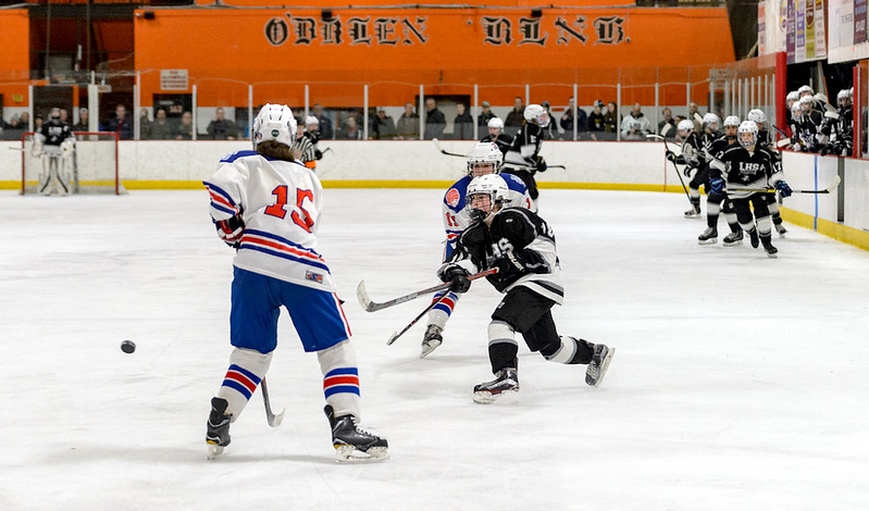 With her teammates on a line change behind her, Kayla Russ rushes up ice and fires a shot on goal