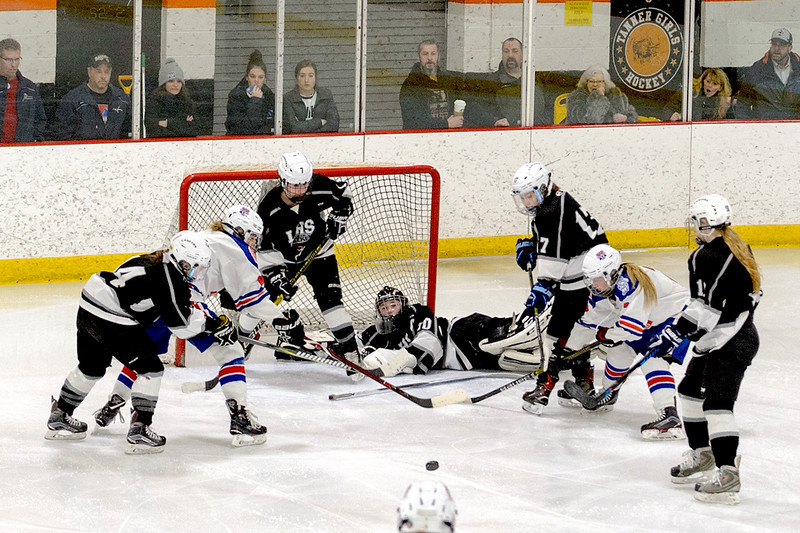 With Methuen buzzing around the net Longmeadow defensemen Madison Manser (14), Madison Fox (7) and forward Kaitlin Quinn (17) keep them from putting in the rebound