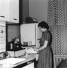 Mary preparing a meal in our Fifth Ave, apartment kitchen. I constructed a platform under the stove and cabinet to achieve a more comfortable working space.