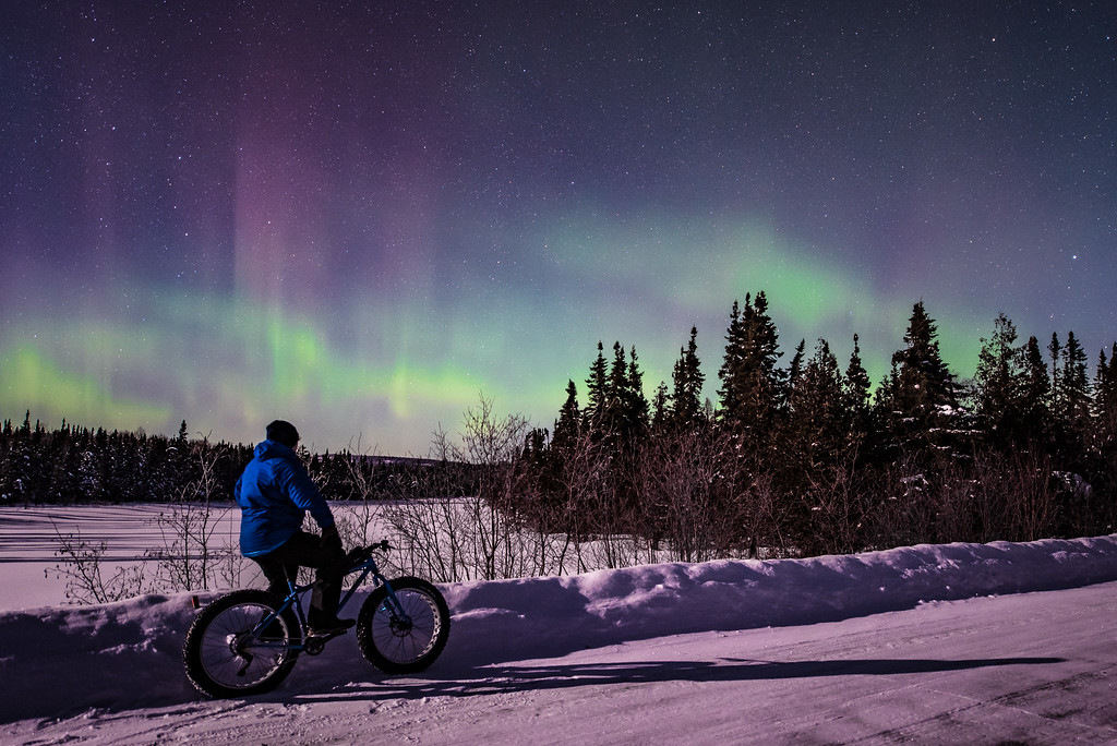 "AURORA 6816<br /> <br /> ""Aurora Borealis Bike Ride""<br /> <br /> What a feeling to be  riding a fat bike on a snowy road illuminated by nothing but moonlight and the glow from the aurora borealis dancing overhead!  This photo was taken at about 1:30 A.M. on February 17, 2016 in the Superior National Forest north of Grand Marais, MN.  What a beautiful night!  I went out in search of the aurora to take pictures of, but I also brought along my bike for a short ride and possible photo op.  I'm glad I brought it because I really like this photo!  I had been riding along one of the gravel forest roads and came upon this clearing with a great view of the sky, so I had to stop for a minute and enjoy the view of the lights."