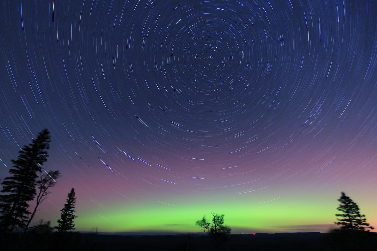 """STAR TRAILS 1985<br /> <br /> """"Aurora Surprise""""<br /> <br /> On the night of September 3rd, 2011 I was out shooting stars and the Milky Way when a quick glance to the North revealed a nice surprise: a faint glow of Northern lights on the horizon!  There wasn't any aurora activity in the forecast that night, so we were quite excited when we looked to the North and saw the lights.  Since they were so faint, I decided to try a long exposure.  This image ended up being 30 minutes long and I just loved the effect of the Northern lights combined with the spinning stars."""