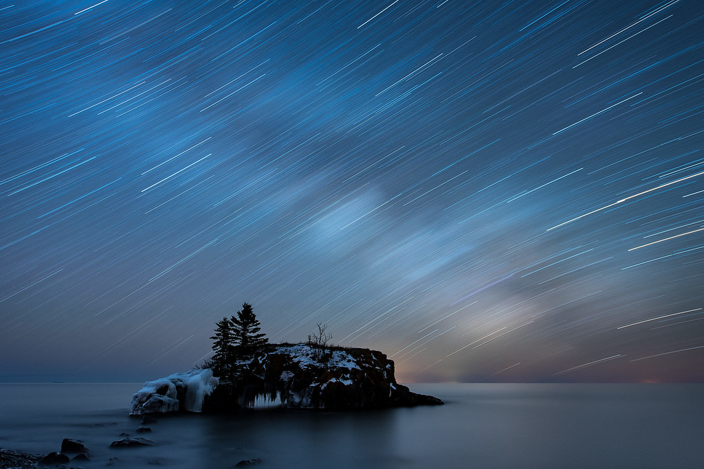 """STAR TRAILS 7378<br /> <br /> """"38 Minutes of the Milky Way""""<br /> <br /> Milky Way star trails over Hollow Rock on Lake Superior in Grand Portage, MN."""