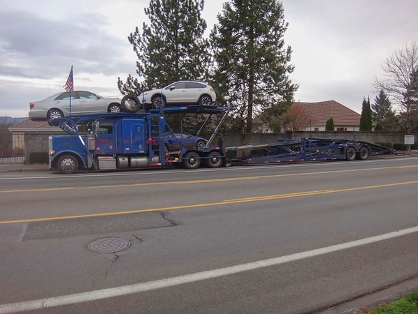 One very small car hidden behind the semi's cab