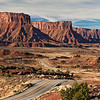 Cliffs and mesas of the Permian Cutler Formation sandstones rise above Utah State Highway 128, about 25 miles northeast of Moab, Utah.