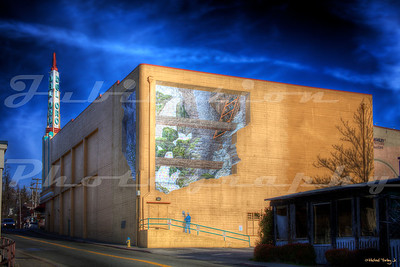 "The Del Oro Theatre, Grass Valley, CA.  Opened in 1942.  This new mural by John Pugh was painted in 2009, and replaced a previous mural of two minors carving a heart out of a big piece of ore.  The heart said, ""Grass Valley - The Heart of the Gold Industry""."