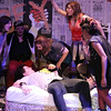 "Left to right, Ariel Saul, Chris Kernan as Jimmy (seated), Evan Fornachon as Johnny (laying on bed), Tanya Sapp, Larissa White, Sarah Porter as Whatsername (partially hidden), and Cameisha Cotton (in front), singing ""Letterbomb,"" in New Line Theatre's AMERICAN IDIOT. Photo credit: Jill Ritter Lindberg."