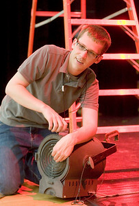 "David Olson, theater director for Sycamore High School and a 2008 SHS graduate, makes adjustments to a stage light prior to a rehearsal of ""Annie Jr."" on Thursday, September 16, 2010."