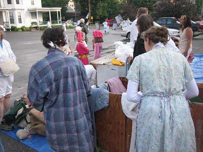 People assemble their costumes.  These are Garbageman and Washerwoman costumes.  They are Everyman-ish archetypes, and in the parades they are strutting around with Vermont secessionist propaganda.  Heee!