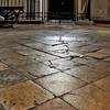 Broken square stone tiles on medieval cathedral floor