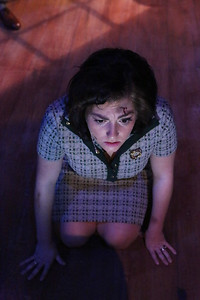 """Sarah Porter as Helen, waiting for the next broadcast from the authorities, in New Line Theatre's """"Night of the Living Dead,"""" 2013. Photo credit: Jill Ritter Lindberg."""