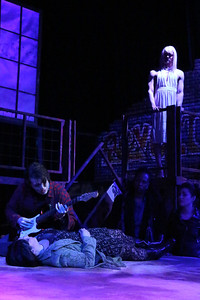 """Evan Fornachon as Roger, singing """"Your Eyes,"""" with Anna Skidis as Mimi in the foreground and Luke Steingruby as Angel, above, in New Line Theatre's """"RENT,"""" 2014. Photo credit: Jill Ritter Lindberg."""