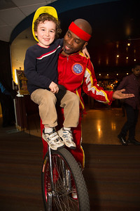 "Kip Jones, leader of the circus' King Charles Troupe teaches Oscar (age 3) to ride the unicycle. King Charles Troupe plays ""high-energy basketball on unicycles in a 'Razzle Dazzle' style,"""