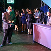 """Zachary Allen Farmer (left foreground) as J.J. Hunsecker and the cast listen as Sean Michael (far right) as Dallas sings """"One Track Mind,"""" in SWEET SMELL OF SUCCESS, New Line Theatre, 2017. Photo credit: Jill Ritter Lindberg."""