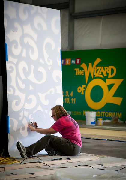Set Designer, Karen Trostad works on the Wicked Witch's gate for the upcoming Wizard of Oz production.  A billboard is near completion in the background.