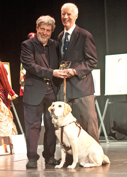 THEATRICAL DESIGN HONOR: scenery, costume and lighting designer Lloyd Burlingame, right, received the 2012 Robert L. B. Tobin Award from the Tobin Theater Arts Foundation.  He and his guide dog Kemp are with the presenter, English set and costume designer Tony Walton, on stage at the Hudson Theater in Manhattan. Burlingame was in his 60s and teaching grad students at New York University when he went blind.