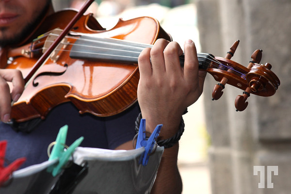 Young man playing the violin on the sidewalk in Mexico City. He's using clothes pins to hold sheet music  - January