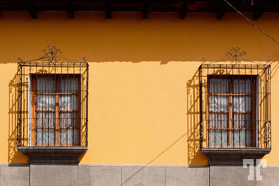 two-windows-on-yellow-wall-antigua-guatemala