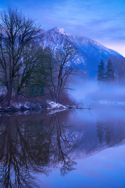 Fog creeps across the pond and begins to fill the Snoqualmie Valley during the blue hour after sunset.