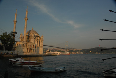 Small boats at sunset near the waterfront Ortakoy Mosque, built in 1853 - 1854, and the Bosphorus Bridge, completed in 1973, connecting Europe (near side) with Asia.