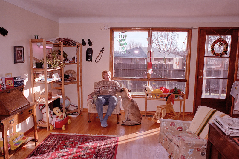 "Room interiors are nostalgia enhancing. This 1987 shot was made in the living room of 1983 Downview Drive in Glenburnie Ontario. I am petting my dog Lady while surrounded by my daughter's toys. The shelves on the left also appear in this interior shot <a href=""https://conceptcontrol.smugmug.com/Themes/Diaries/Recollections/i-3Lk2DvM/A""> (click here)</a> taken in Edmonton. They, along with the decorations on the walls and much of the furniture in the room were dragged across Canada when we moved east."