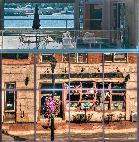 This is a single photo of a building across the street from the camera in Dartmouth, Nova Scotia, Canada. The woman at top is on a terrace looking across to the far shore, and below is a reflection in the building.
