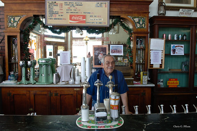Carrizozo, New Mexico - Now converted to Roy's Giftshop, this old drugstore still uses the original fountain.  Roy poses behind the fountain.