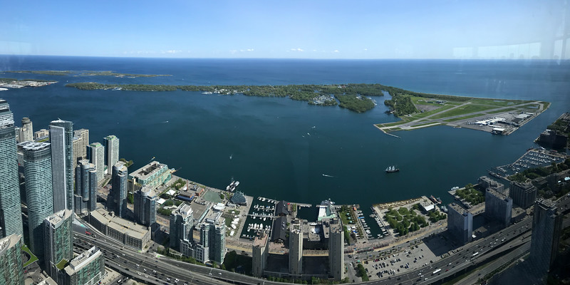 "An iPhone panorama of Toronto Island from the CN Tower. There are two general tower observation decks. The lower one is ""wired in"" and the upper is ""glassed in.""  In both cases, you cannot get an unobstructed view.  Here glass reflections and distortions degrade what could have been a pretty decent panorama."