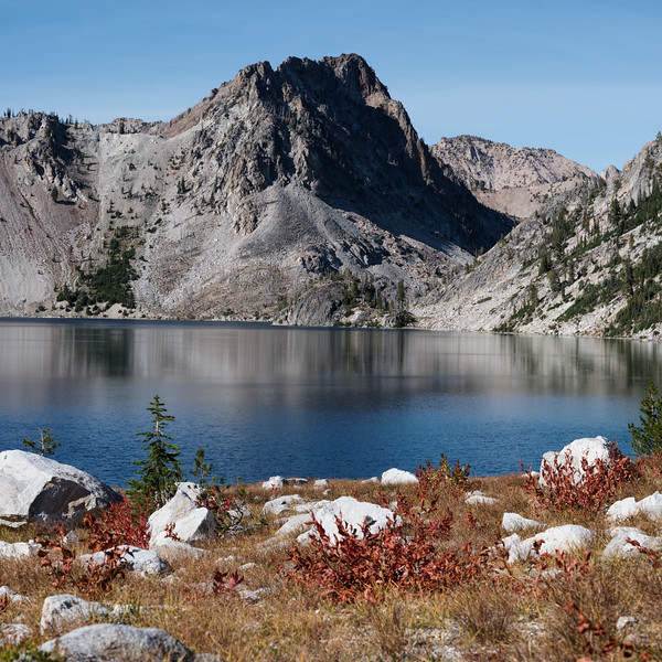 Looking northwest from the southern end of Sawtooth Lake. The mountains get a touch of autumn colors. The red bushes in the foreground contrasted nicely with the blue of the lake.