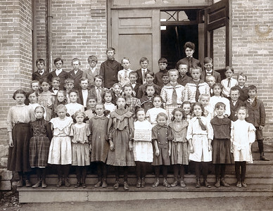 I found this 1907 Dickinson High School class portrait, (a girl in the front row is holding a sign), in my grandmother Helen's prints. I am not sure where this school was and I doubt that either my grandmother Helen, who was only five years old in 1907 or my grandfather Frank, nine at the time, were in this class. I started restoring this shot without thinking about the large number of faces I would have to inspect. I removed spots on every single face! There is still work to do here. The brick background is stained but I didn't feel like fixing hundred-year-old bricks. Why bother you ask? I like the expressions on the kid's faces and old pictures like this shove our mortality in our faces. Every single person in this photograph has long since died. They had their lives, however long, and now most, if not all, are completely forgotten leaving only old photographs to mark their faces.