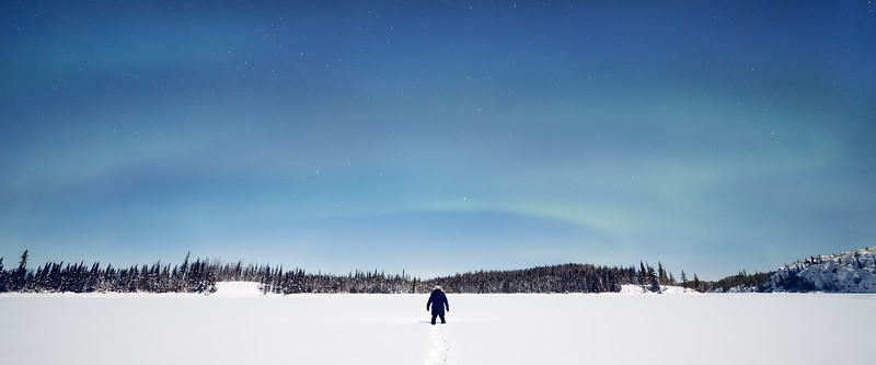 Yellowknife, Vee Lake - Man in middle of frozen lake under soft aurora