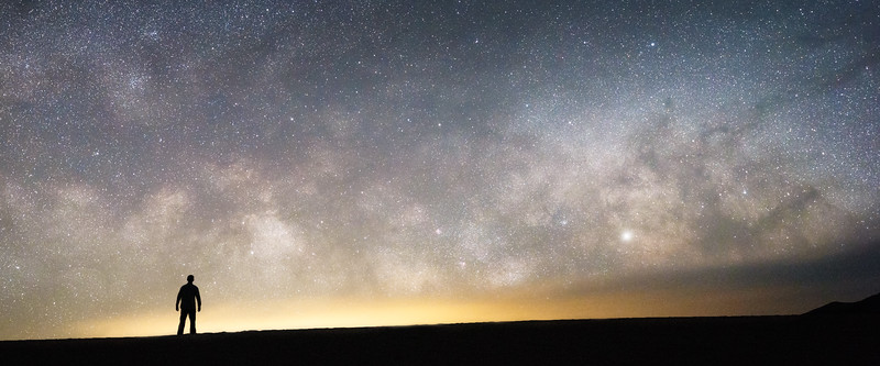 Death Valley, Mesquite Flat - Milky Way with man standing on dune in silhouette
