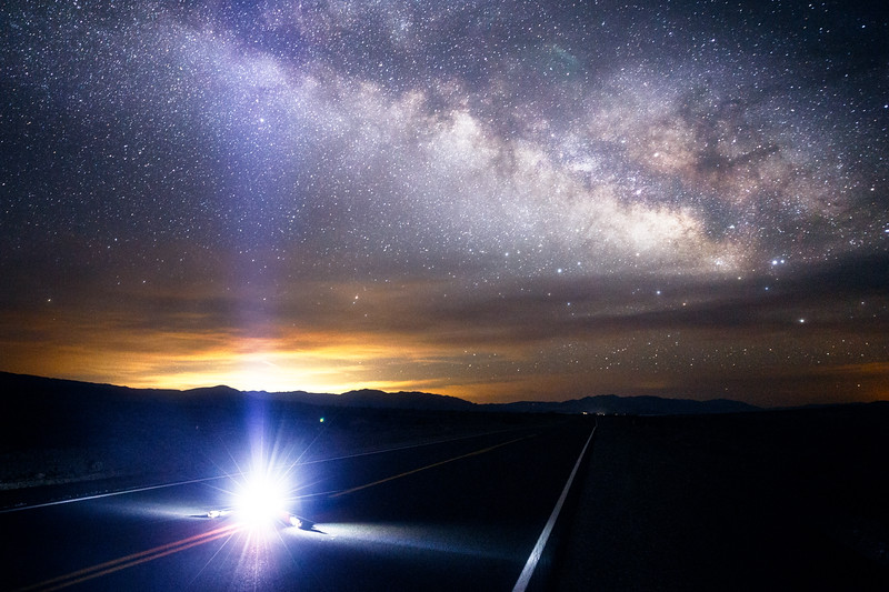 Death Valley, Furnace Creek - Milky Way with man lying in road with headlamp
