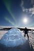 Yellowknife, Vee Lake - Man standing next to igloo under aurora