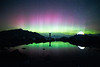 Whatcom, Artist Point - Man standing with arms up next to illuminated tent next to lake with colorful aurora