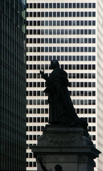 Statue silhouette in front of Montreal office buildings.