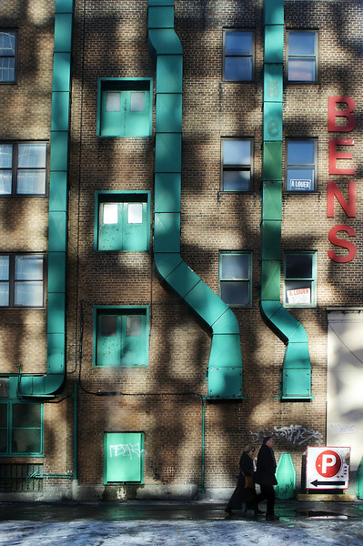 Sunlight from neighboring buildings falling on green ducts.