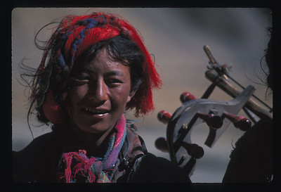 Closeup of Tibetan nomad, with home made musical instrument.