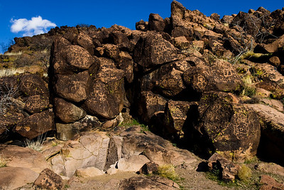 "Petroglyphs, Mojave National Preserve, California.  The natural depression in the foreground collects water from higher elevations.  These watering holes or ""Tinjas"" attracted native Americans who left their mark on the surrounding rock."